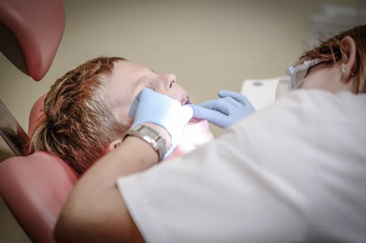Dentists in Glasgow City centre wearing rubber gloves look into little boys mouth as he lies on the dental chair.